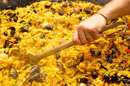 main du cuisinier dans plat de paëlla espagnol